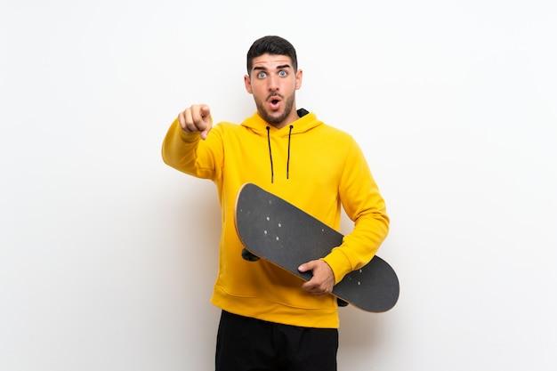 孤立した白い壁にハンサムな若いスケーター男が驚いて、正面を指す
