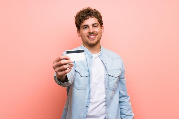 クレジットカードを保持しているピンクの壁の上の金髪の男