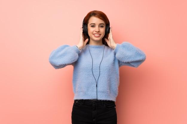 ヘッドフォンで音楽を聴くピンクの壁の上の若い赤毛の女性