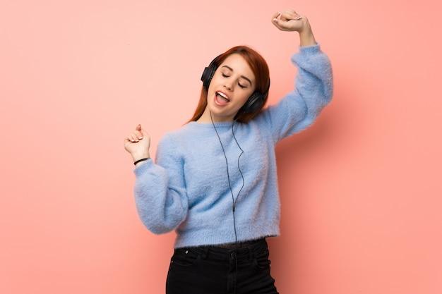Рыжая молодая женщина над розовой стеной слушает музыку в наушниках и танцует