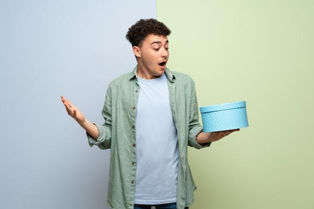 手でギフトボックスを保持している青と緑の壁の上の若い男