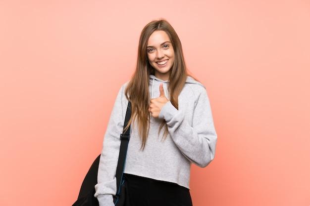 ジェスチャーを親指を与える分離のピンクの壁の上の若いスポーツ女性