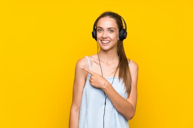 製品を提示する側を指している孤立した黄色の壁で音楽を聴く若い女性