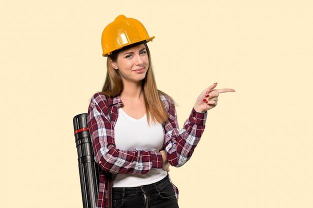 孤立した黄色の壁を越えて側に指を指す建築家女性