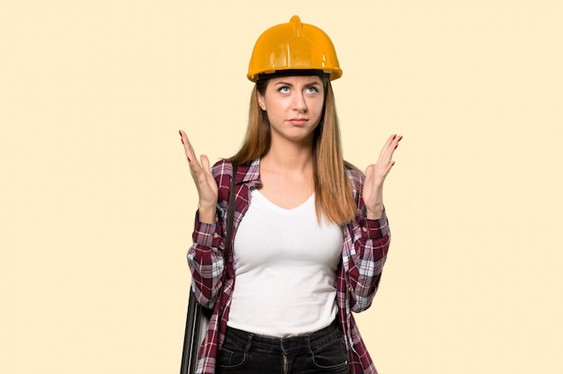 孤立した黄色の壁の上の悪い状況に不満の建築家女性