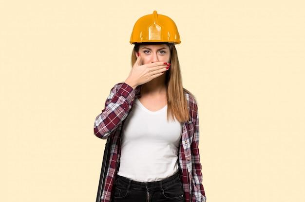 孤立した黄色の壁に何か不適切なことを言って手で口を覆っている建築家女性
