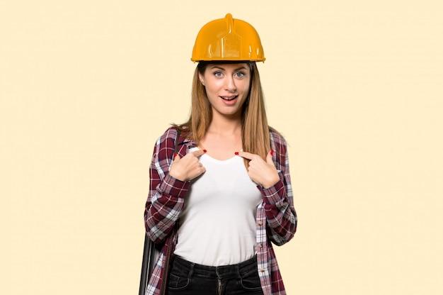 孤立した黄色の壁の上の驚きの表情を持つ建築家女性