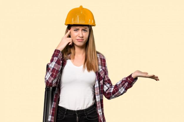 孤立した黄色の壁を頭に指を置いて狂気のジェスチャーを作る建築家女性