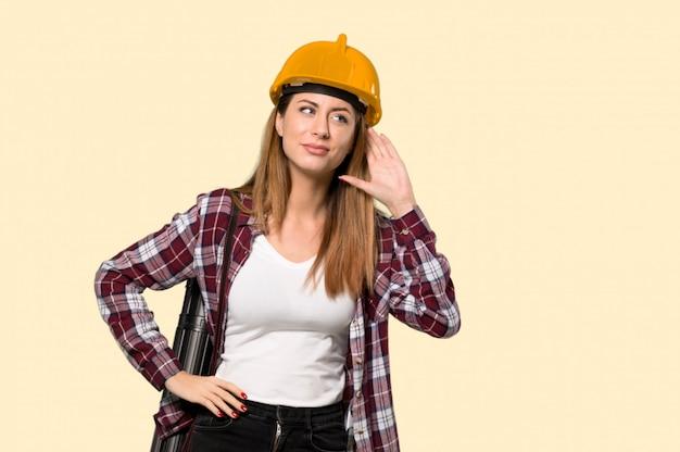 孤立した黄色の壁の上の耳に手を置くことで何かを聞いて建築家女性
