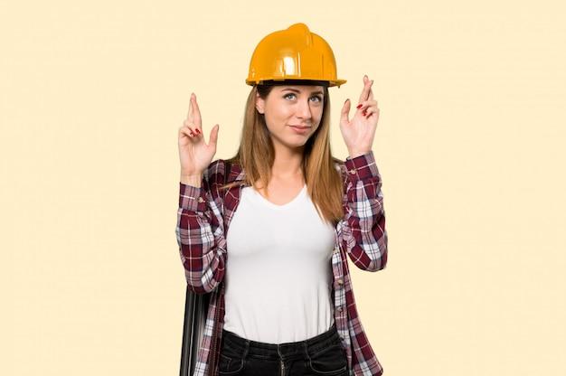 交差点と孤立した黄色の壁を越えて最高を望む指で建築家の女性