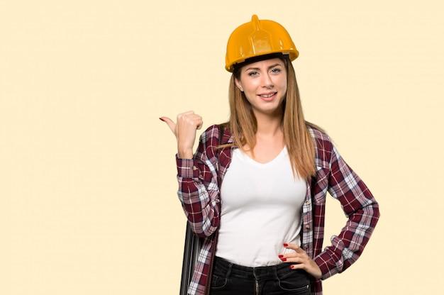 孤立した黄色の壁を越えて製品を提示する側を指している建築家女性