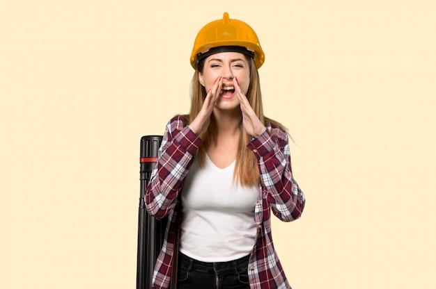 孤立した黄色の壁の上に何かを叫んで発表する建築家女性