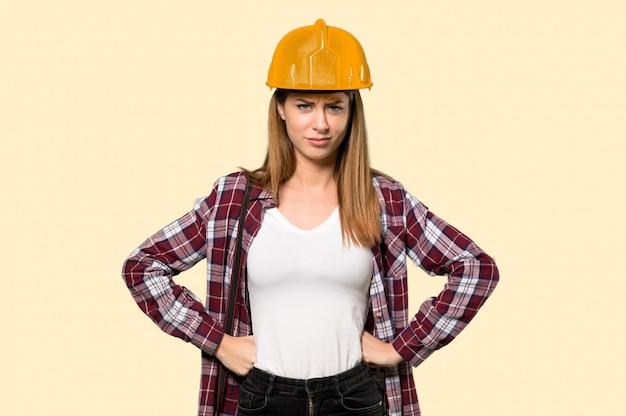 孤立した黄色の壁に怒っている建築家女性
