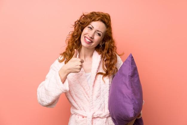 ジェスチャを親指を与えるドレッシングガウンの赤毛の女性
