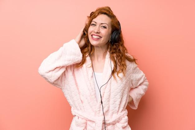 音楽を聴くドレッシングガウンの赤毛の女性