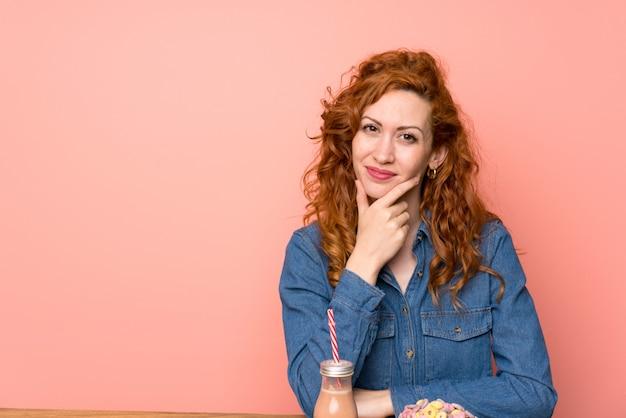 赤毛の女性が朝食用シリアルと果物に立って、アイデアを考えて