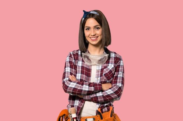 孤立したピンクの壁に正面の位置で交差腕を維持する若年労働者の女性