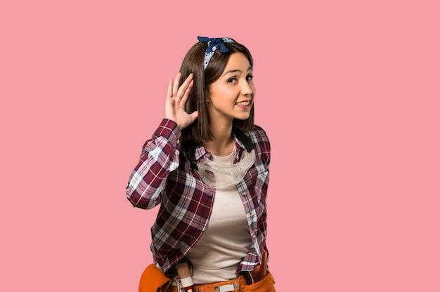 孤立したピンクの壁に耳に手を置くことによって何かを聞いて若年労働者の女性