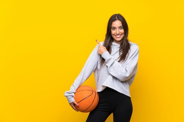Молодая женщина играет в баскетбол над желтой стеной, указывая в сторону, чтобы представить продукт