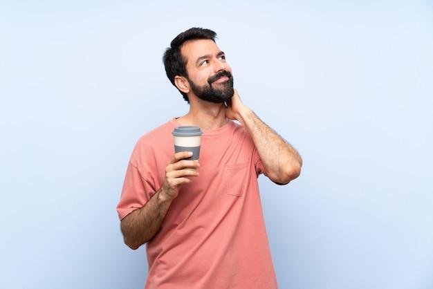 Молодой человек с бородой, держа прочь кофе на изолированных синей стене, думая, идея