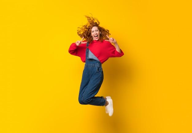 孤立した黄色の壁を飛び越えてオーバーオールで赤毛の女性