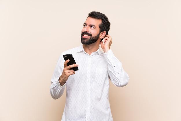 Молодой человек с бородой держит мобильный мышления идея