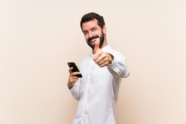 何か良いことが起こったため、親指で携帯電話を保持しているひげを持つ若者