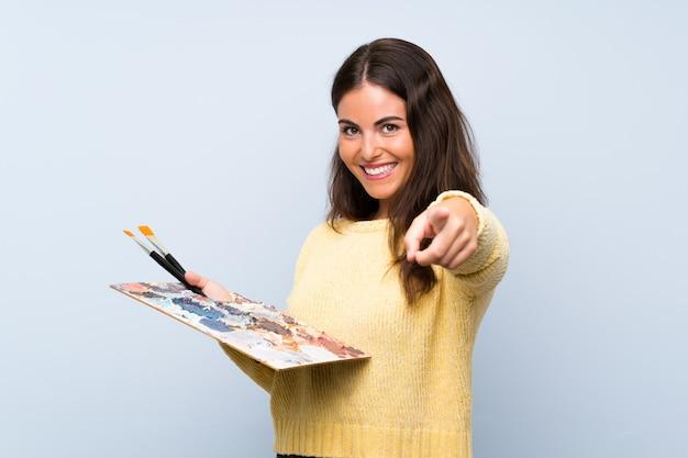 孤立した青い壁の上の若いアーティストの女性が自信を持って表現であなたに指を指す