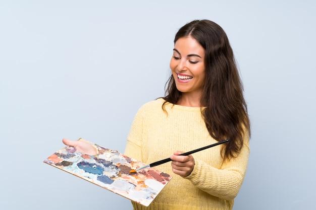 孤立した青い壁の上の若いアーティストの女性