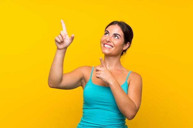 人差し指で素晴らしいアイデアを指している孤立した黄色の壁の上の若い女性