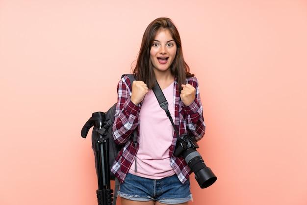 勝利を祝う孤立したピンクの壁の上の若い写真家の女の子