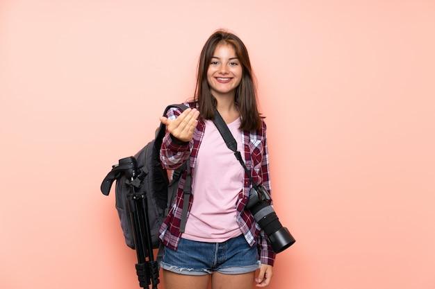 来て招待して孤立したピンクの壁の上の若い写真家の女の子