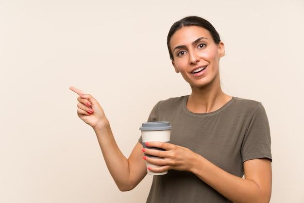 Молодая женщина, держащая прочь кофе удивлен и указывая пальцем в сторону