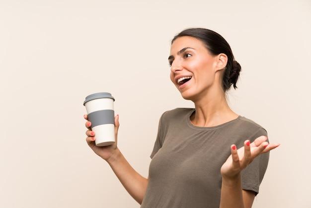 Молодая женщина, держащая прочь кофе с удивлением выражением лица