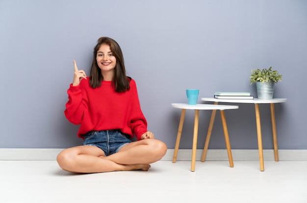 人差し指で素晴らしいアイデアを指している床に座っていた若い女性