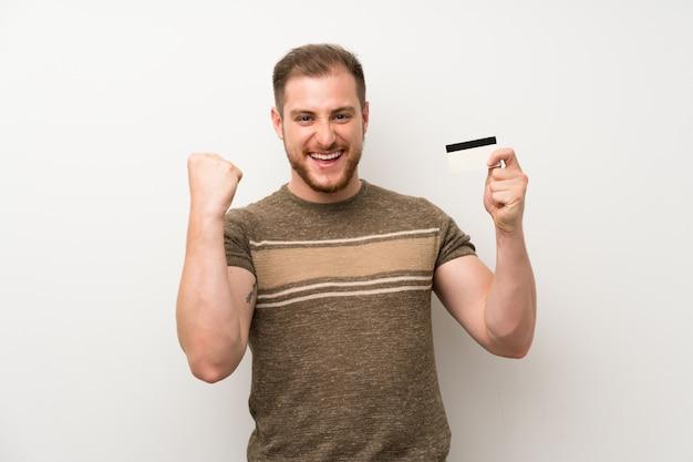 クレジットカードを保持している孤立した白い壁の上のハンサムな男