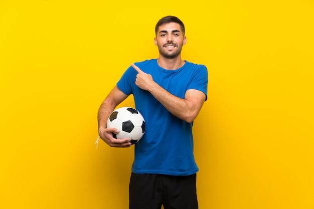 製品を提示する側を指している孤立した黄色の壁の上の若いハンサムなフットボール選手男