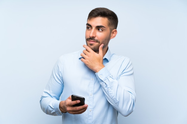 Молодой красивый человек с его мобильным телефоном над изолированной голубой стеной думая идея