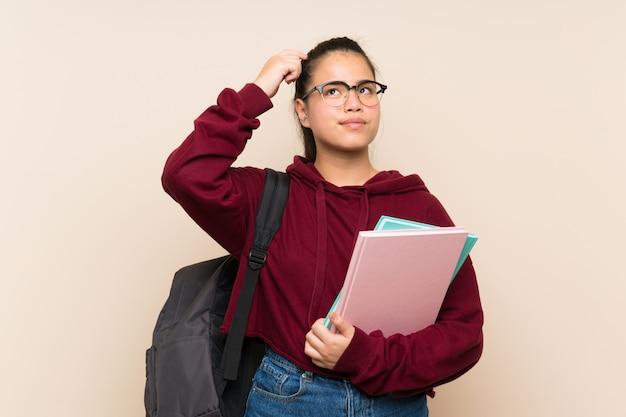 若い学生のアジアの女の子の女性の疑わしいと混乱の表情を持つ孤立した壁を越えて