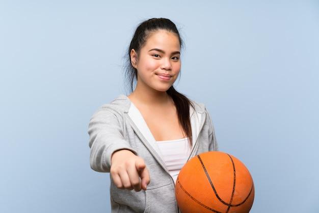 Молодая азиатская девушка играет в баскетбол над изолированной стеной указывает пальцем на вас с уверенностью выражения