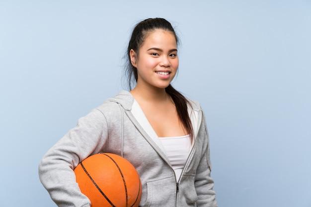 Молодая азиатская девушка играя баскетбол над изолированной стеной
