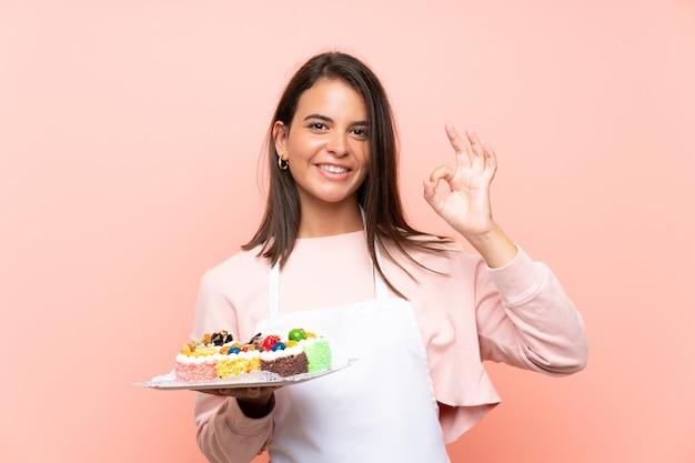Молодая девушка держит много различных мини-пирожных над изолированной стеной, показывая знак ок с пальцами