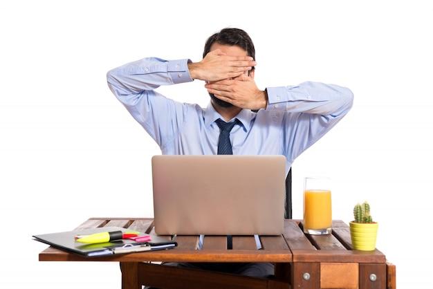 Бизнесмен в своем кабинете, закрыв лицо