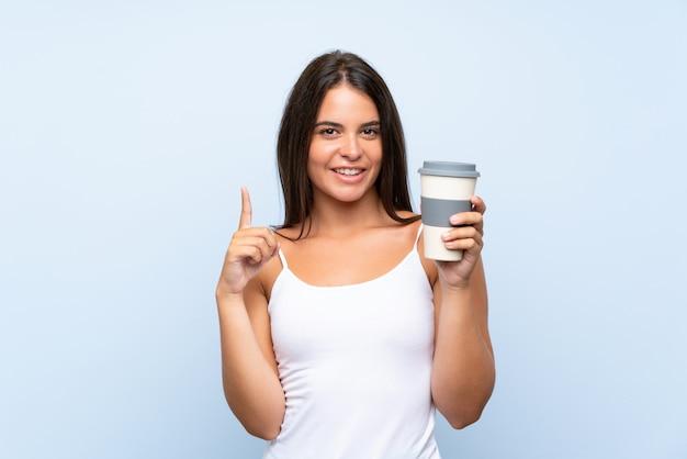 素晴らしいアイデアを指している分離の青い壁にテイクアウェイコーヒーを保持している若い女性