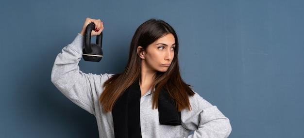 ケトルベルを持つ若いスポーツ女性