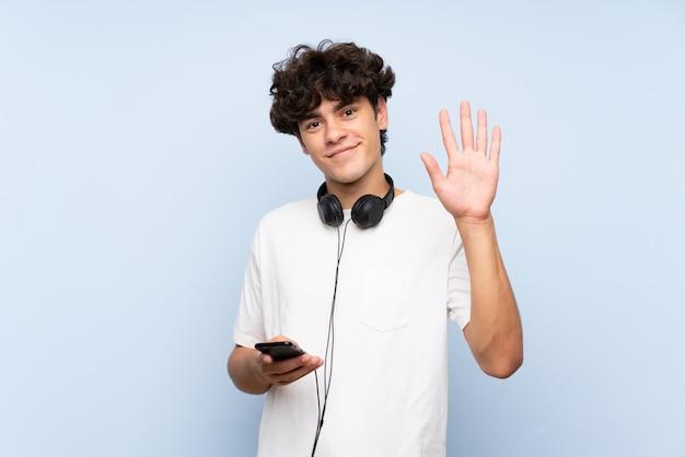 若い男が幸せな表情で手で敬礼分離の青い壁に携帯電話で音楽を聴く