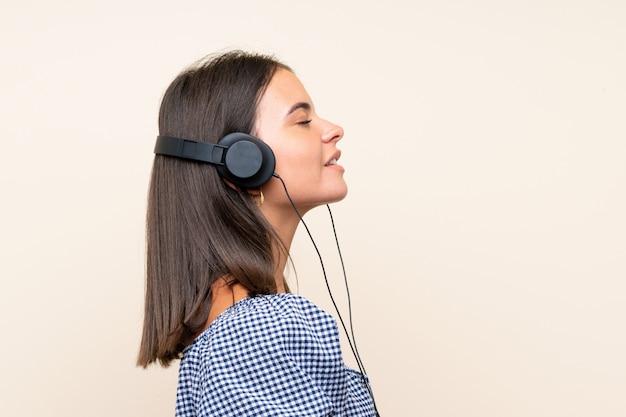 ヘッドフォンで音楽を聴く孤立した壁の上の少女