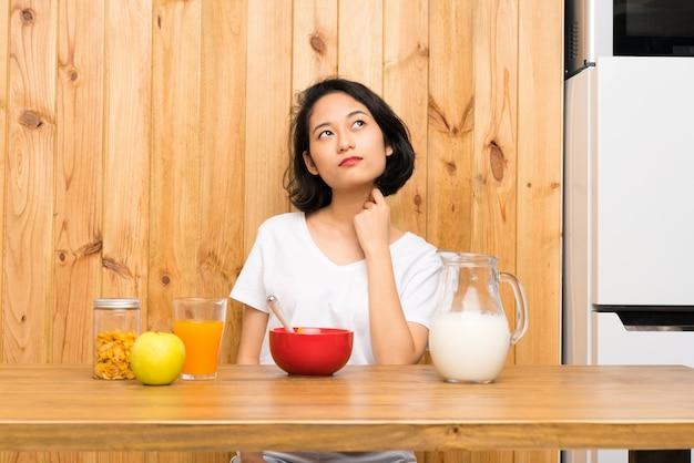アイデアを考えて朝食牛乳を持つアジアの若い女性