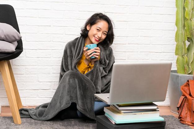 Азиатская молодая женщина, сидя на полу, держа чашку кофе