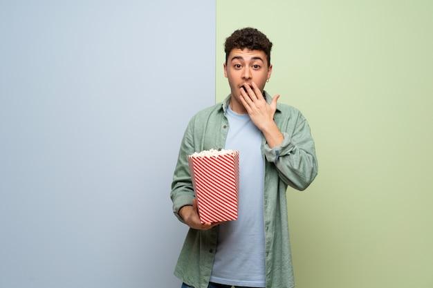 Молодой человек на синей и зеленой стене удивлен и ест попкорн